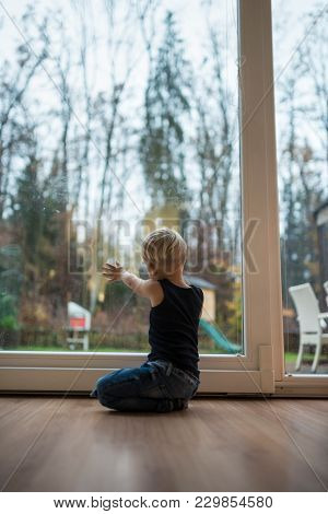 Little Blond Boy Kneeling On A Wooden Floor At Home In Front Of A Glass Patio Door Overlooking The G