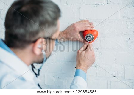 Doctor Listening Heartbeat Of Toy Heart With Stethoscopes