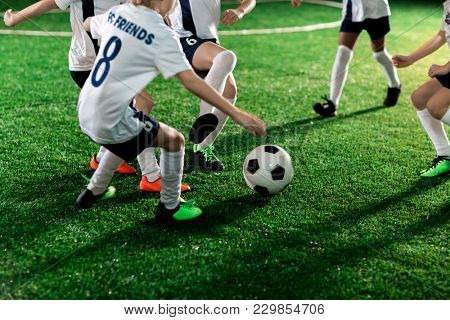 Football team of several active boys running throughout pitch after ball during game