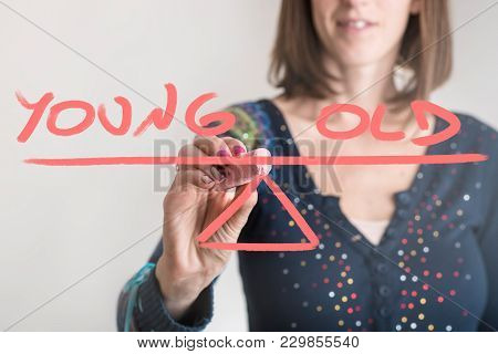 Young - Old Balance Concept With A Businesswoman Drawing A Seesaw With Text On A Virtual Screen In A