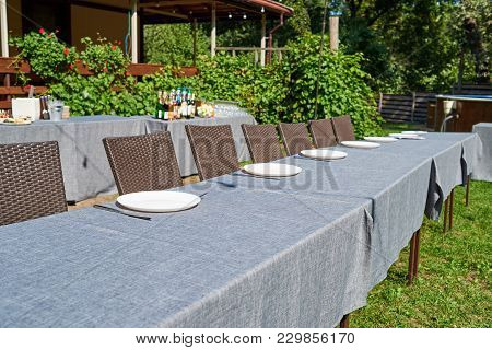 Dinner Table With Empty Ceramic Round Plates And Cutlery On Grey Tablecloth And Chairs Outdoors, Cop