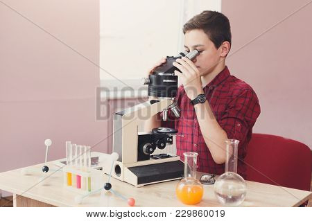 Schoolboy Looking In Microscope During Lesson Of Chemistry Or Biology In School. Stem Education. Ear