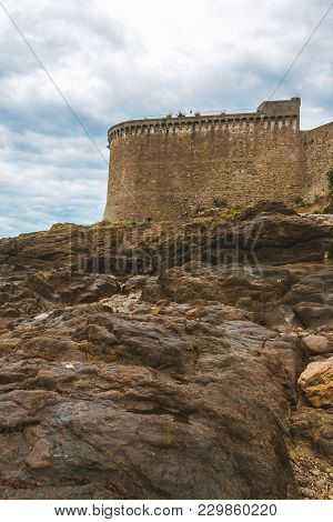 Low Angle Shot Of High Fortification Walls Of Saint-malo, Brittany, France  And Huge Rocks In Foregr