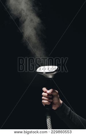 Close-up Partial View Of Person Holding Garment Steamer With Steam On Black