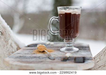 A Cup With A Hot Drink In The Winter Forest. Hot Cocoa With Cinnamon On The Background Of Winter For