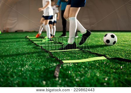 Legs of youthful football players during exercising on professional facilities on green pitch