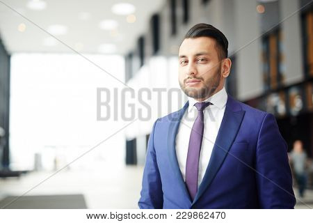 Young confident delegate in formalwear looking at camera in modern airport
