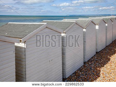 Row of white wooden cabins on shingle beach at popular seaside resort Bexhill-on-Sea in East Sussex South East England UK