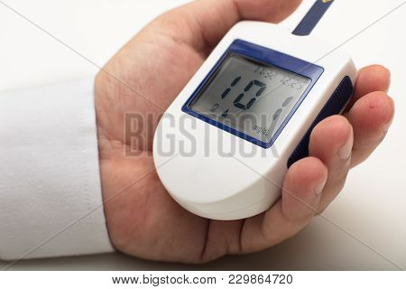 Man With Diabetes Holding A Portable Digital Glucose Meter In His Hand As He Measures His Own Blood