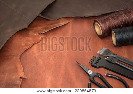 Tools For Leather Crafting And Pieces Of Brown Leather. Manufacture Of Leather Goods. View From Abov