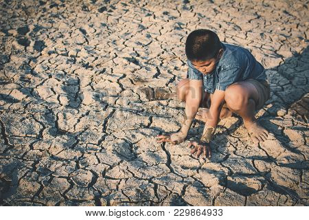 Sad Boy Sitting On Cracked Dry Ground, Concept Drought