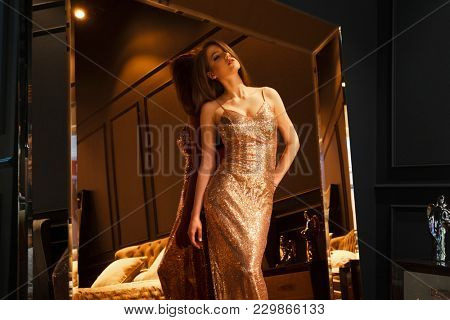 Golden mirror, Vogue fashion style portrait of young beautiful pretty elegant rich woman wearing evening gold dress in luxury apartments