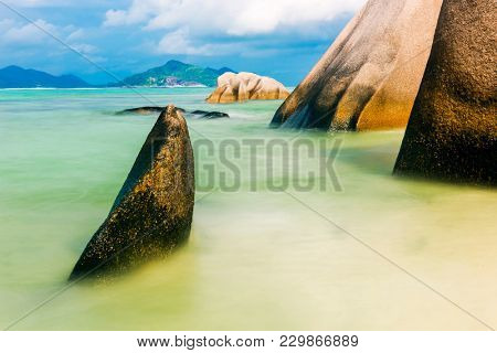 Beautifully shaped granite boulders in the sea of Seychelles at Anse Source d'Argent beach taken with a long exposure. Dramatic stormy sky