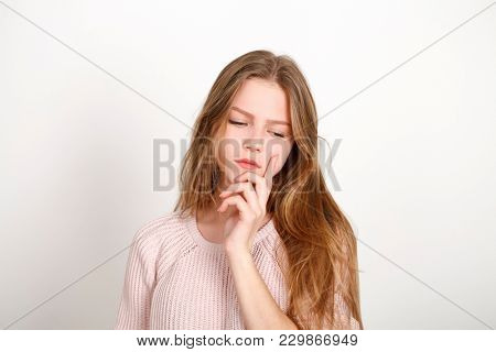 Attractive Blonde Girl with her Hands on her Face, isolated on white wall background
