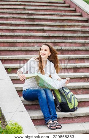 Young Travelling Woman Sitting With Map On Stairs In Old European Town