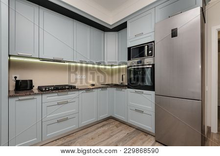 Modern white and black kitchen, electric oven and gas stove, minimalistic clean design