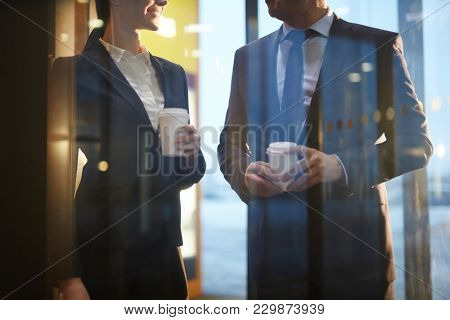 Two colleagues in formalwear having coffee and talking behind transparent wall inside modern building