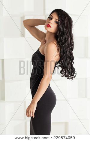 Elegant Brunette Woman With Wavy Hair. Female Model In Black Cocktail Dress