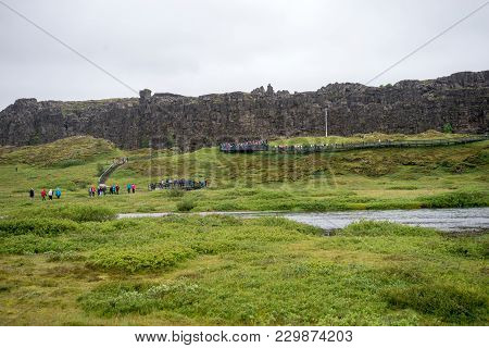 Thingvellir, Iceland - July 19, 2017: Tourists Walk Through The Almannagja Fault Line In The Mid-atl
