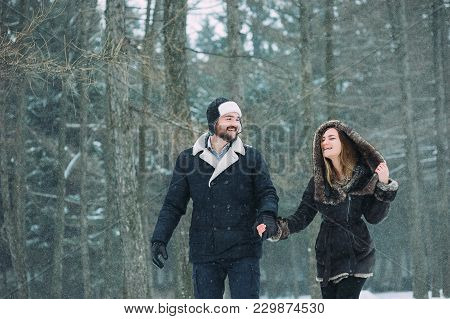 Guy And Girl Walking And Having Fun In The Snowy Forest