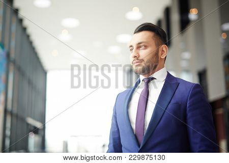 Young elegant diplomat in suit and tie looking forwards inside modern building