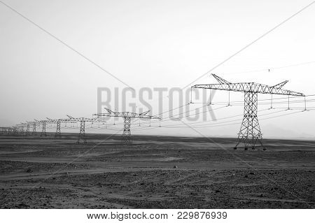 Electricity Pylons And High Voltage Power Lines In Sand Desert Land Surface On Evening Blue Sky Back