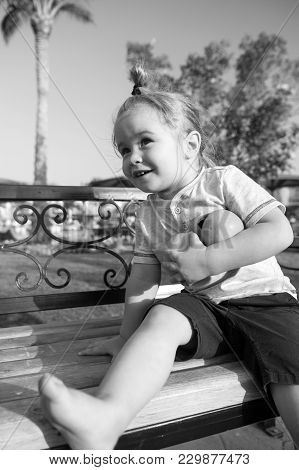 Child. Small Little Baby Boy Sitting With Two Oranges On Bench On Sunny Day In Park. Kid With Blond
