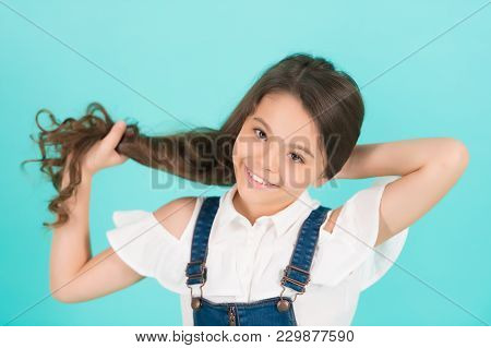 Child Smile With Healthy Brunette Hair. Girl Hold Long Hair On Blue Background. Haircare, Hairstyle