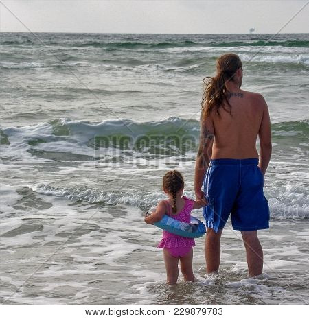 Daddy Taking His Small Daughter Out In The Gulf Of Mexico For The First Time. He Holds Her Hand As H