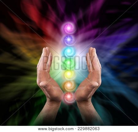 Sending Chakra Healing Energy - Male Parallel Hands Facing Upwards Against A Multicoloured Backgroun