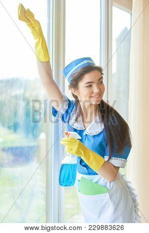 Cheerful Housemaid Cleaning A Window. Girl Using Glass Detergent. Eco Friendly Home Cleaning Product