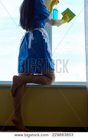 Legs Of Young Housemaid. Attractive Woman Cleaning Window.