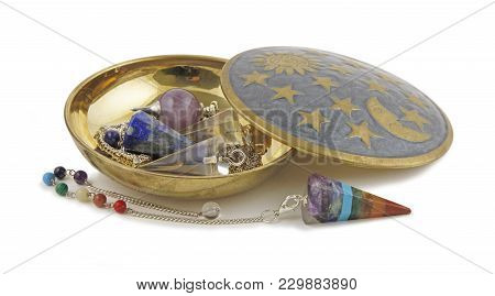 Selection Of Radionics Dowsing Pendants - Brass Dish On A White Background Containing Three Differen