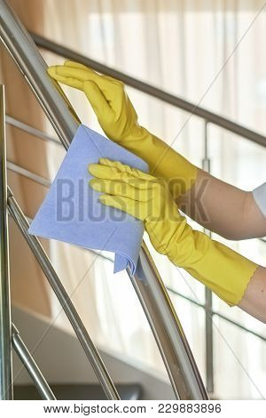 Hands In Gloves And Rag. Woman Wiping Railing. Cleaning Tips From The Pros.