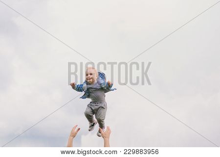 Man Hands High Toss Up Little Cute Child Baby Boy On Blue Clouds Sky Background. Father Rest, Have F