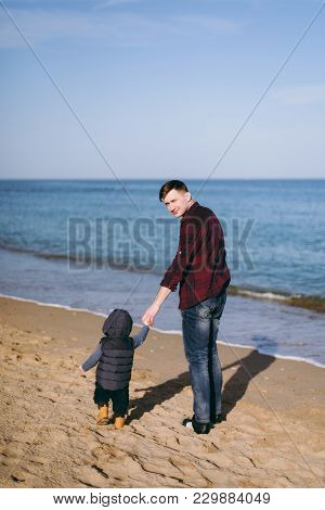 Young Man Standing At Sea Sand Beach Background Holding Hand Little Cute Child Baby Boy, Looking On