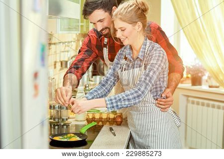 Cheerful Man And Woman Cooking. Fried Eggs And Herbs. Quick And Healthy Recipes.