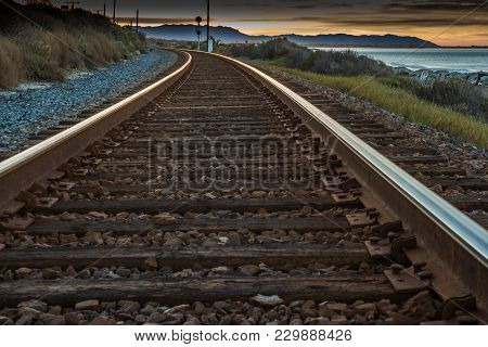 Train Tracks Heading Toward The Sunrise Curve Out Of View Along The Ocean.