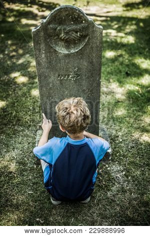 Young boy in front of an old grave inscribed with the word
