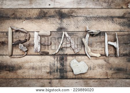 Beach sign made of driftwood on a wooden background