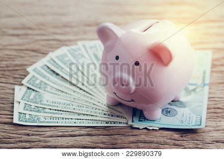 Finance, Banking, Saving Money Account, Pink Piggy Bank On Pile Of Us Dollar Banknotes On Wooden Tab
