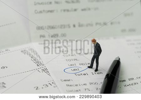 Miniature Business Man Figurine Standing On Printed Payment Invoice, Bill Or Receipt And Looking At