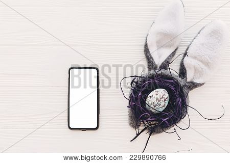 Phone With Empty Screen And Bunny Ears And Stylish Egg In Nest On White Wooden Background Flat Lay.
