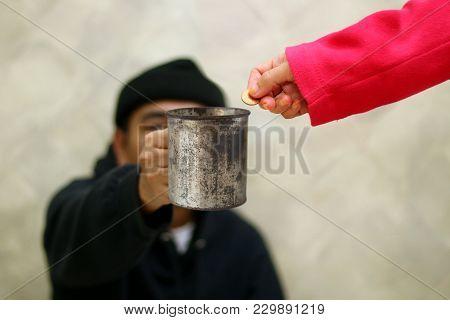 Women Hand Giving Money To Beggar On The Street Walkway