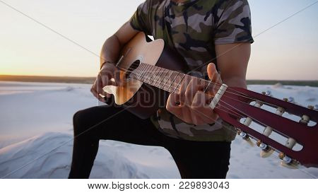 Close-up Portrait Of Young Arab Man Who, With Smile On Face, Plays Favorite Melody On Musical String