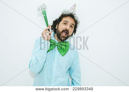 Portrait Of Man With Party Hat, Noisemakers And Big Green Tie.