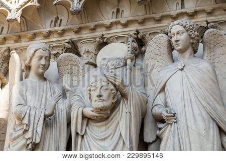 Architectural details of Cathedral Notre Dame de Paris on Cite island in Paris Saint Denis holding his head