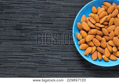 Almond In Blue Plate On Dark Background. Brown Almond For Food. Organic Food Banner Template With Te