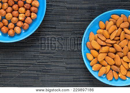Almond And Hazelnut In Blue Plate On Dark Background. Ripe Almond For Food. Organic Food Banner Temp