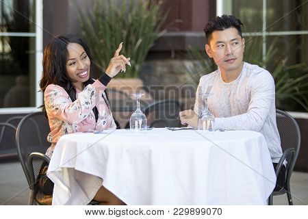 Interracial couple on a date ordering from a waiter in an outdoor restaurant.  The image depicts ser